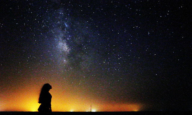 A woman looks at the Milky Way galaxy rising in the night sky in Kuwait's al-Salmi desert, 120Km north of the capital, on August 9, 2021. (Photo by Yasser Al-Zayyat/AFP Photo)