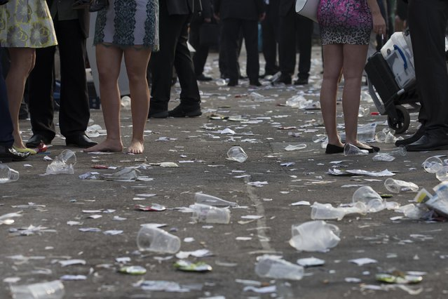 Race goers stand amongst litter after Aintree race meeting's Ladies Day at Aintree Racecourse Liverpool, England, Friday, April 10, 2015. The Grand National horse race is scheduled for Saturday at Aintree. (Photo by Jon Super/AP Photo)