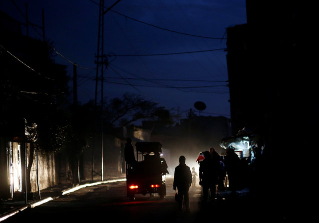 Palestinians walk on a street during a power cut in Beit Lahiya in the northern Gaza Strip January 11, 2017. (Photo by Mohammed Salem/Reuters)