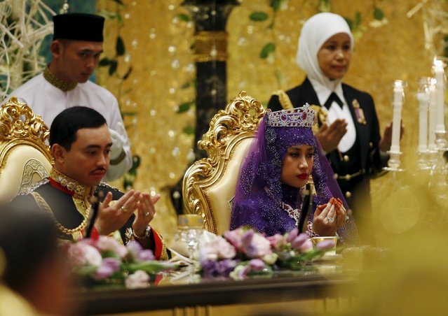 Brunei's newly wed royal couple, Prince Abdul Malik and Dayangku Raabi'atul 'Adawiyyah Pengiran Haji Bolkiah,  pray at the royal wedding banquet at the Nurul Iman Palace in Bandar Seri Begawan April 12, 2015. (Photo by Olivia Harris/Reuters)