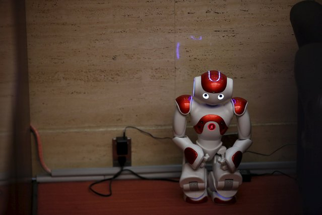 "A ""Nao"" humanoid robot by Aldebaran Robotics sits in a corner while its batteries are being charged during a presentation at a branch of the Bank of Tokyo-Mitsubishi UFJ (MUFG) in Tokyo April 13, 2015. (Photo by Thomas Peter/Reuters)"