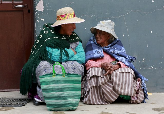 Elderly indigenous women chat at a polling center during a national referendum in El Alto, on the outskirts of La Paz, Bolivia February 21, 2016. Bolivians voted on Sunday in a referendum that will decide if President Evo Morales can stay in power for a fourth term. (Photo by David Mercado/Reuters)