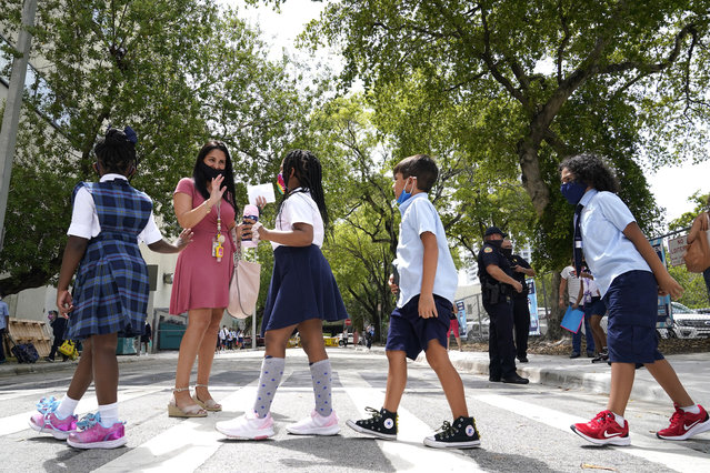 Teacher Vanessa Rosario greets students outside of iPrep Academy on the first day of school, Monday, August 23, 2021, in Miami. Schools in Miami-Dade County opened Monday with a strict mask mandate to guard against coronavirus infections. (Photo by Lynne Sladky/AP Photo)