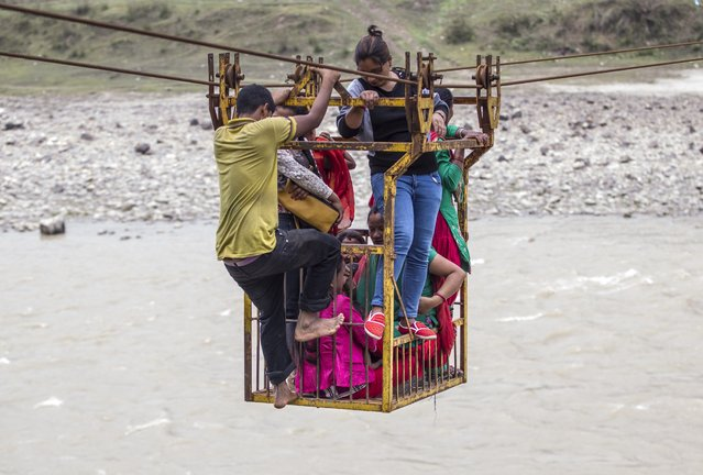 Group of Nepalese use rope bridge as they  crossing the Trishuli river, near the Fhading Village in Dhading Disrict, some 90 kilometers from capital Kathmandu, Nepal. 14 April 2015. Farmers, students and villagers from the other side of the Trishuli river have to use different methods to cross the river after local authorities failed to build a promised bridge. (Photo by Narendra Shrestha/EPA)