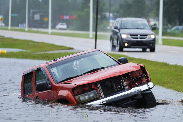 An abandoned vehicle is half submerged in a ditch next to a near flooded highway as the outer bands of Hurricane Ida arrive Sunday, August 29, 2021, in Bay Saint Louis, Miss. (Photo by Steve Helber/AP Photo)