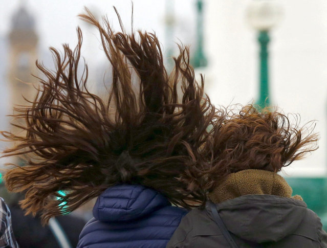Two women walk with their fly-away hair during a windy day in San Sebastian, the Basque Country, northern Spain, 27 February 2016. The Iberian Peninsula is under a spell of rough weather with strong winds and snow level rising in the north and centre of the country. (Photo by Juan Herrero/EPA)