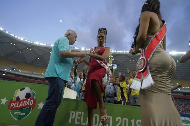 "Peladao soccer tournament organizer Arnaldo Santos helps runner-up beauty contestant Rayssa Santos off the podium as the crown's winner Isabelle Nogueira looks on during the Peladao tournament at Arena da Amazonia in Manaus, Brazil, Saturday, February 16, 2019. ""I want other girls to feel proud when they look at me, a girl coming from the slums, with black and indigenous blood, taking part in the contest to be Queen of the Peladao"", said Santos, a 21-year-old mixed-race university student. ""I didn't get it this year, but I will keep trying"". (Photo by Victor R. Caivano/AP Photo)"