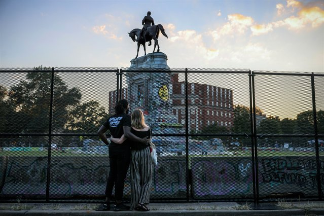 Richmond residents look at the statue of Confederate General Robert E. Lee, the largest Confederate statue remaining in the United States, the day before the monument will be removed in Richmond, Virginia, U.S., September 7, 2021. (Photo by Evelyn Hockstein/Reuters)