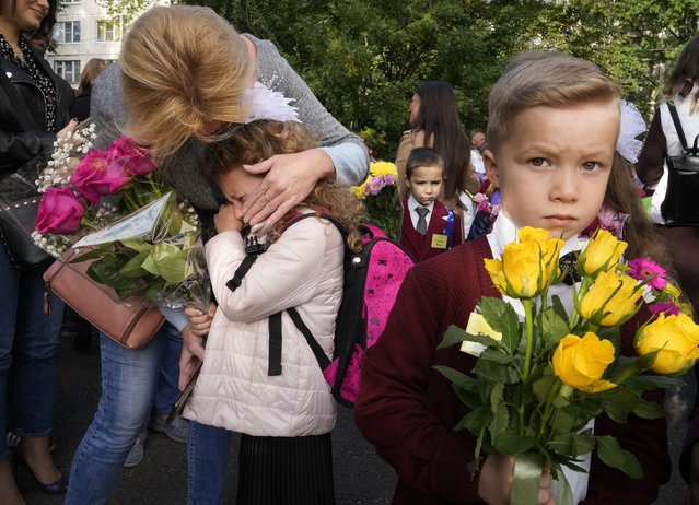 """A girl in the first grade cries during a ceremony marking the start of classes at a school as part of the traditional opening of the school year known as """"Day of Knowledge"""" amid the ongoing COVID-19 pandemic in St. Petersburg, Russia, Wednesday, September 1, 2021. (AP Photo/Dmitri Lovetsky)"""