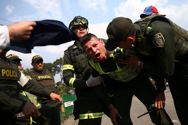 A Colombian police officer affected by tear gas reacts during clashing between opposition supporters and Venezuela's security forces at Simon Bolivar bridge on the border line between Colombia and Venezuela, as seen from Cucuta, Colombia, February 25, 2019. (Photo by Edgard Garrido/Reuters)