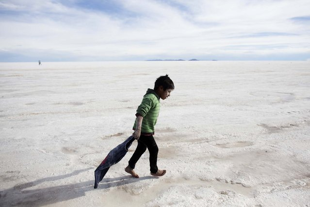 A boy walks on the Uyuni Salt Flats after bathing in a hole with salty water in Uyuni, Bolivia on January 11, 2014. The motorcycles and quads of the Dakar Rally raced through parts of the Uyuni Salt Flats two days later. (Photo by Victor R. Caivano/Associated Press)