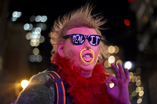 """A protester wearing a Donald Trump mask demonstrates during a """"Queer Rage"""" dance party outside the location of the 2017 """"Congress of Tomorrow"""" Joint Republican Issues Conference in Philadelphia, Pennsylvania, U.S. January 25, 2017. (Photo by Mark Makela/Reuters)"""