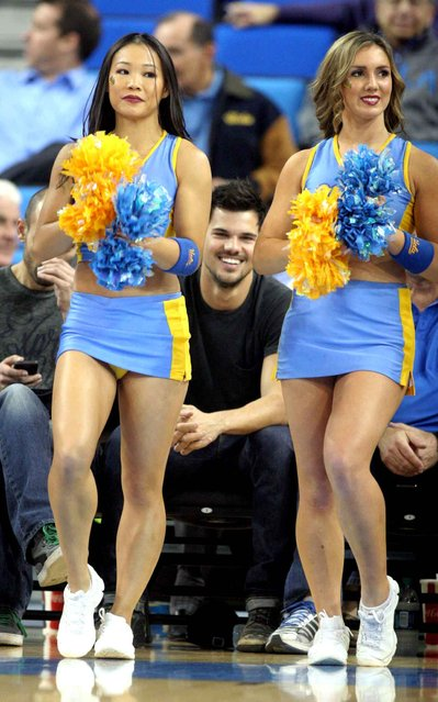 Taylor Lautner sits court side at the UCLA vs. Stanford basketball game with a few pals on Thursday evening in Los Angeles, on January 24, 2014. (Photo by WENN/SIPA Press)