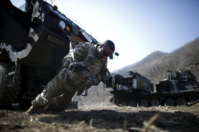 A U.S. army soldier exercises in front of a M270A1 multiple launch rocket system as they prepare for a live-fire training exercise of the 6-37th Field Artillery Regiment at a training area near the demilitarized zone separating the two Koreas, in Cheorwon, South Korea, March 9, 2016. (Photo by Kim Hong-Ji/Reuters)