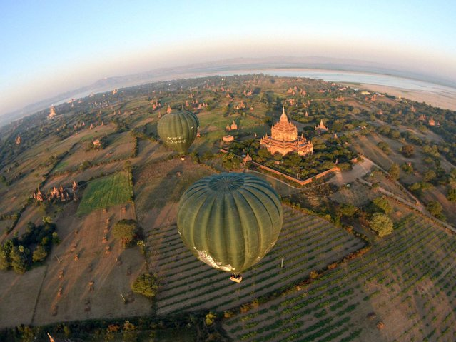 Hot air balloons provide a view of the temples as they hovers over Bagan in Myanmar on February 4, 2014. Between the 11th and 13th centuries, Bagan in Mandalay province in Myanmar was the kingdom's capital, one of the most important centres for learning in Asia, if not the world. The kings and rulers built thousands of temples, more than 3,000 of which are still standing today. (Photo by Ye Aung Thu/AFP Photo)
