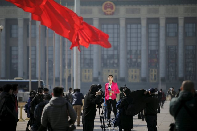 A reporter is lit with bounced light while reporting outside the Great Hall of the People before the closing ceremony of the Chinese People's Political Consultative Conference (CPPCC) in Beijing, China, March 14, 2016. (Photo by Damir Sagolj/Reuters)