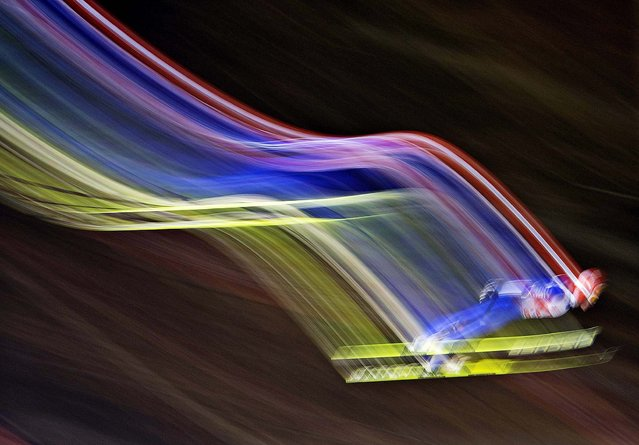 In this picture taken with a time exposure Richard Freitag of Germany soars through the air during the qualification at the FIS World Cup ski jumping in Willingen, Germany, Friday, January 31, 2014. (Photo by Jens Meyer/AP Photo)