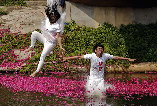 Groom Praem Pam Srichamnan and his bride Suriya Utai jump into a pond during a wedding ceremony ahead of Valentine's Day in Prachin Buri province, east of Bangkok February 13, 2014. Three Thai couples took part in the wedding ceremony arranged by a resort aimed to strengthen the relationships of the couples by doing fun activities. (Photo by Damir Sagolj/Reuters)