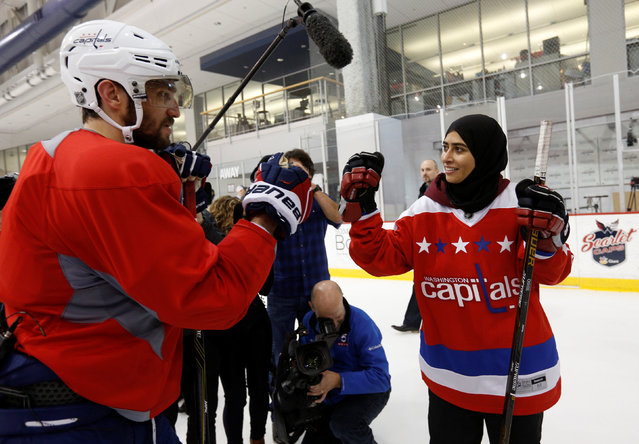 Fatima Al Ali of United Arab Emirates fist bumps Washington Capitals hockey star Alex Ovechkin after she played with the team during their practice in Arlington, Virginia, U.S. February 8, 2017. (Photo by Kevin Lamarque/Reuters)
