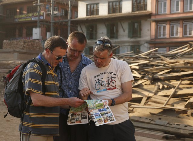Tourists check the map in Durbar Square which was destroyed by the earthquake in Kathmandu, Nepal, May 5, 2015. (Photo by Olivia Harris/Reuters)