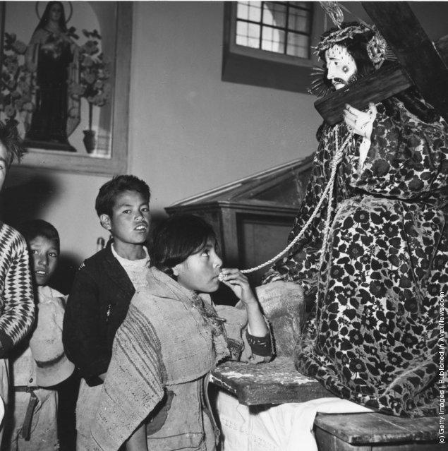 Peruvian children kissing a sculpture of a suffering Christ, 1955