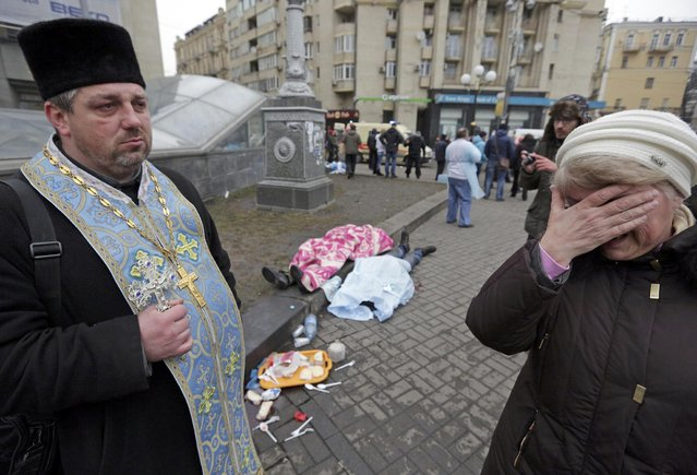 An Orthodox priest holds a cross as a woman reacts next to dead bodies following violence in Independence Square in Kiev February 20, 2014. (Photo by Konstantin Chernichkin/Reuters)