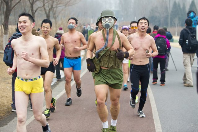 A runner jogs while wearing a diving mask in the Third Undie Run in the Olympic Greens in Beijing, China 23  February 2014. Over 200 participants strip down to their underwear  in the freezing cold  and haze to run to promote environmentally friendly lifestyles. (Photo by Zhao Bing/EPA)