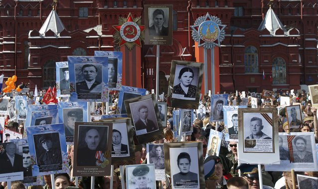 People take part in Immortal Regiment march with pictures of World War Two soldiers on Red Square during the Victory Day celebrations in Moscow, Russia, May 9, 2015. (Photo by Maxim Shemetov/Reuters)