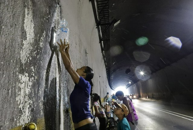 A woman collects water from a spout in a highway tunnel, in Caracas, Venezuela, Monday, April 1, 2019. (Photo by Ariana Cubillos/AP Photo)