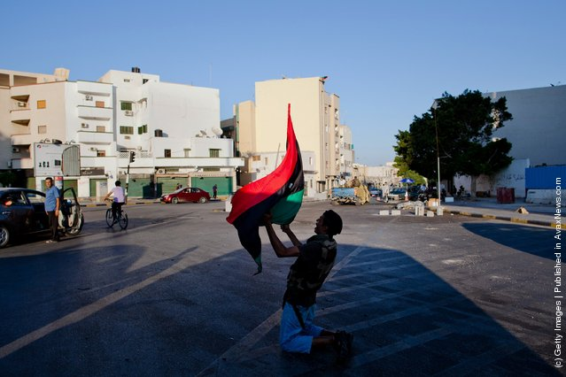 A Libyan Rebel fighter yells anti-Gaddafi slogans as he celebrates in the street
