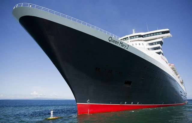 Captain Kevin Oprey (bottom L) standing beneath the soaring hull of Cunard's flagship Queen Mary 2, on March 6, 2014. (Photo by James Morgan/AFP Photo)