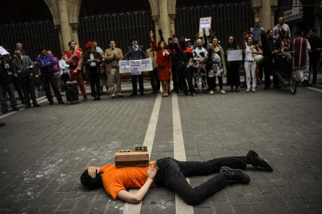 A man lies on the street covered with bricks on his back, during a performance against corruption,  in Pamplona, northern Spain, Thursday, May 14, 2015, prior to the Regional Spanish Elections to be held on May 24. (Photo by /Alvaro Barrientos/AP Photo)