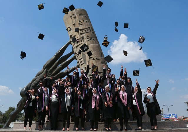 """University of Baghdad graduates throw their caps in the air while posing for a group photo next to the """"save Iraqi culture"""" monument, in Baghdad, Iraq, Wednesday, March 27, 2019. (Photo by Hadi Mizban/AP Photo)"""