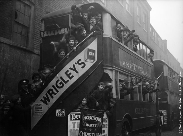 1931: 150 children from the Hoxton Market Mission in London set off for Queens Gate by bus to attend a Christmas tea and gift-giving session at the mansion of Mr C A Simpson. The rear bus sports a large poster advertising Wrigley's Chewing Gum