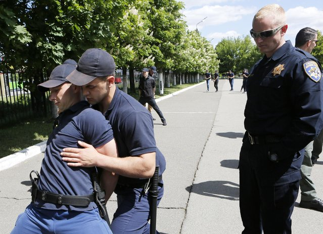 An American policeman supervises training at a National Academy of Internal Affairs in Kiev, Ukraine, Saturday, May 16, 2015. U.S. Assistant Secretary of State Victoria Nuland is in Ukraine this week to hold talks with the country's top officials and oversee their efforts at transforming the Ukrainian police into a modern police force. (Photo by Sergei Chuzavkov/AP Photo)