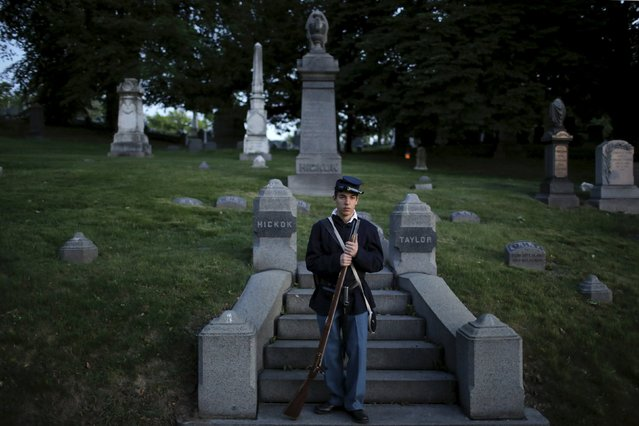 A uniformed re-enactor stands guard next to a grave during a ceremony to mark 150th anniversary of the end of the civil war and memorial day celebrations at Green-Wood Cemetery in Brooklyn, New York May 23, 2015. (Photo by Eduardo Munoz/Reuters)