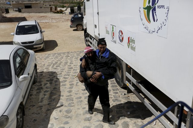 A man carries his brother with amputated legs towards a mobile truck clinic in the rebel-controlled area of Maaret al-Numan town in Idlib province, Syria March 20, 2016. (Photo by Khalil Ashawi/Reuters)
