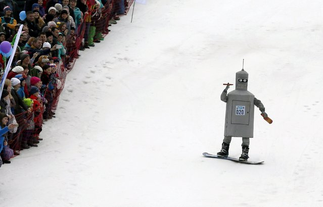"""Spectators watch a snowboarder in a fancy costume, slides down before an attempt to cross a pool of water at the foot of a ski slope at the Bobrovy Log ski resort on the suburbs of the Siberian city of Krasnoyarsk, Russia, April 17, 2016. Skiers and snowboarders took part in the annual """"Gornoluzhnik"""" amateur event marking the end of the ski season at the Siberian resort. (Photo by Ilya Naymushin/Reuters)"""