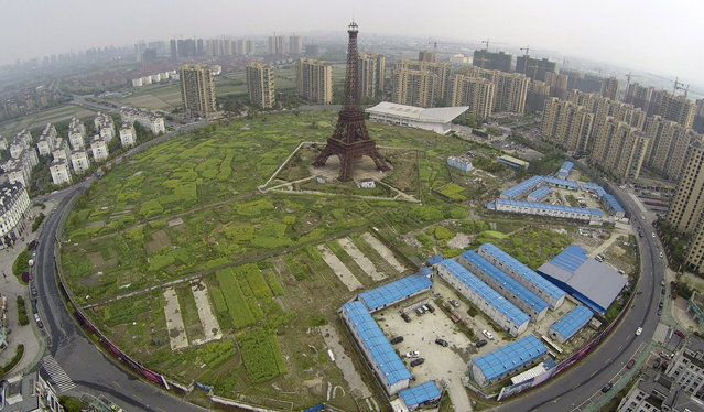 An aerial view shows a replica of the Eiffel Tower (C) and residential buildings at the Tianducheng development in Hangzhou, Zhejiang province April 8, 2015. (Photo by Reuters/Stringer)