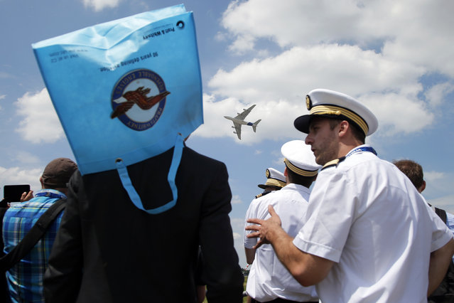 The Airbus A380 performs a demonstration flight as onlookers , one of them wearing a bag as a sun hat, at the Paris Air Show, in Le Bourget airport, north of Paris, Tuesday, June 16, 2015. Some 300,000 aviation professionals and spectators are expected at this weekends Paris Air Show, coming from around the world to make business deals and see dramatic displays of aeronautic prowess and the latest air and space technology. (AP Photo/Francois Mori)