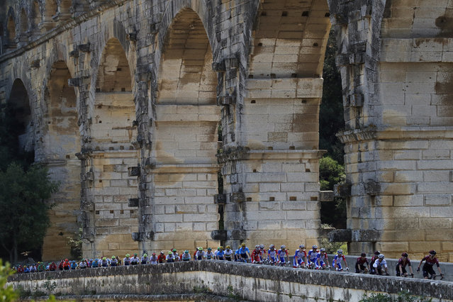 The pack rides next to the Pont du Gard during the sixteenth stage of the Tour de France cycling race over 117 kilometers (73 miles) with start and finish in Nimes, France, Tuesday, July 23, 2019. (Photo by Christophe Ena/AP Photo)