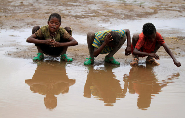 Children wash their heads with rain water in Kobo village, one of the drought stricken areas of Oromia region, in Ethiopia, April 28, 2016. (Photo by Tiksa Negeri/Reuters)