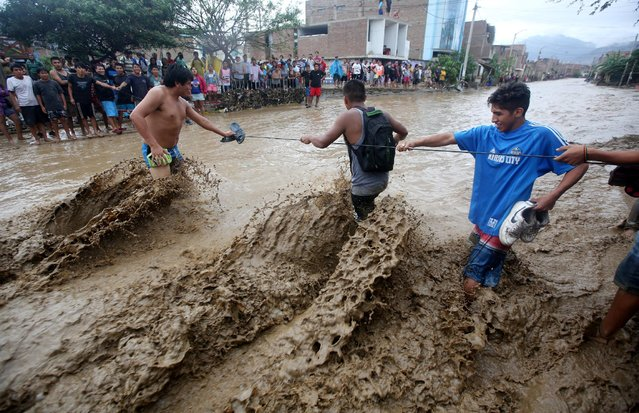 Residents cross a street after a massive landslide and flood in Trujillo, northern Peru, March 19, 2017. (Photo by Douglas Juarez/Reuters)
