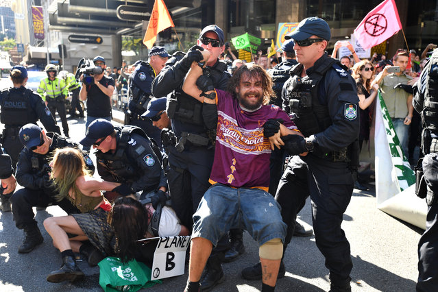 Police arrest Extinction Rebellion protesters after they blocked the corner of Edward Street and Queen Street on August 06, 2019 in Brisbane, Australia. Climate change activists blocked off streets in the Brisbane central business district today causing traffic delays. According to reports approximately 10 activists have been arrested by police for blocking traffic. (Photo by Darren England/AAP)