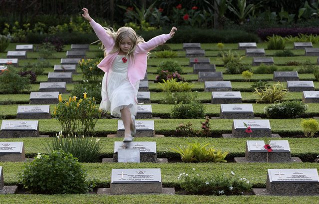 A girl leaps over headstones at the Jakarta War Cemetery following the ANZAC Day dawn service in Jakarta, Indonesia, Friday, April 25, 2014. ANZAC Day honors the men of the Australia-New Zealand Army Corps who died in World War I at the 1915 battle for Gallipoli, Turkey. It has since come to honor the sacrifices made by all service members in the Australian and New Zealand Armed Forces. (Photo by Mark Baker/AP Photo)
