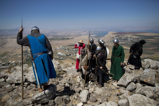 In this Saturday, July 4, 2015 photo, Israeli and Russian members of knight clubs get ready for the reenactment of the Battle of Hattin in Horns of Hattin, northern Israel. (Photo by Oded Balilty/AP Photo)
