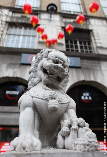 A stone Chinese dragon statue stands in the street in the Chinatown area of Westminster