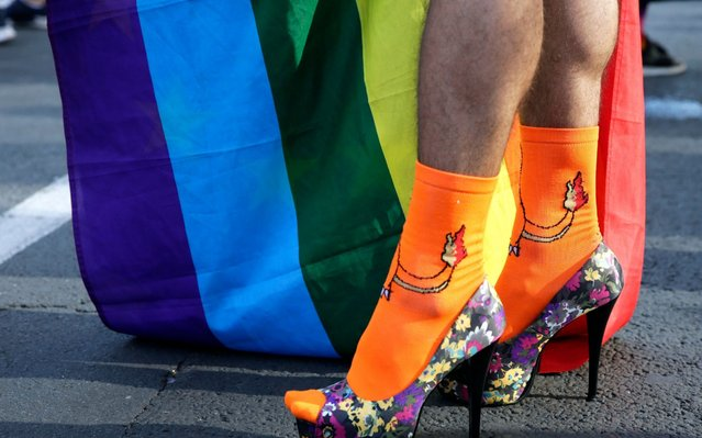 """A participant in high heel shoes during the Belgrade Pride Parade march in Belgrade, Serbia, 15 September 2019. Holding rainbow colored flags, balloons and banners with slogans such as """"I'm not giving up"""" pride participants marched the 10th time through the main streets of Serbia's capital near the main institutions in the city to which Belgrade Pride has been addressing its demands for improved rights for the LGBTI+ community. (Photo by Andrej Cukic/EPA/EFE)"""