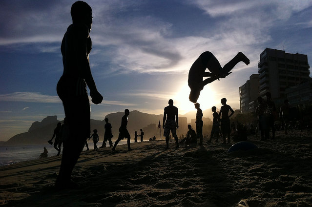 A man performs a flip on Ipanema Beach on May 1, 2014 in Rio de Janeiro, Brazil. The 2014 FIFA World Cup starts in Brazil on June 12. (Photo by Mario Tama/Getty Images)