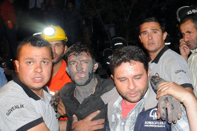 Medics help a rescued miner after an explosion and fire at a coal mine killed at least 17 miners and left up to 300 workers trapped underground, in Soma, in western Turkey, Tuesday, May 13, 2014, a Turkish official said. Twenty people were rescued from the mine but one later died in the hospital, Soma administrator Mehmet Bahattin Atci told reporters. The town is 250 kilometers (155 miles) south of Istanbul. The death toll was expected to rise. (Photo by AP Photo/Depo Photos)